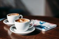 Två koppar av cappuccino med lattekonst på trätabellen royaltyfri foto