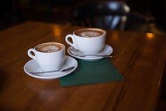Två koppar av cappuccino på en trätabell arkivbilder