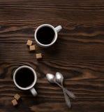 Två koppar av espresso med stycken av rottingsocker Arkivbilder