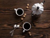 Två koppar av espresso med stycken av rottingsocker och italienarekaffebryggaren Fotografering för Bildbyråer