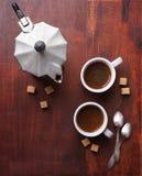 Två koppar av espresso med stycken av rottingsocker och italienarekaffebryggaren Arkivfoto