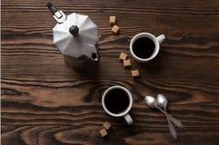 Två koppar av espresso med stycken av rottingsocker och italienarekaffebryggaren på tabellen Arkivfoton