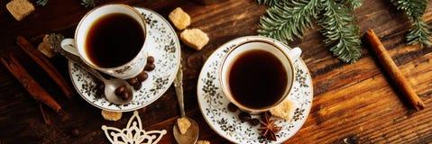 Två koppar av espresso med stycken av rottingsocker och italienarekaffebryggaren på trätabellen arkivfoto