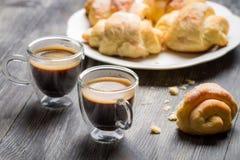 Två koppar av espresso och giffel för frukost Arkivfoton