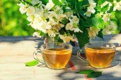 Två koppar av grönt te med jasminblommor Royaltyfri Bild
