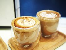 Två koppar av Latte med Lattekonst i ett dubbelt isolerat exponeringsglas Arkivfoto