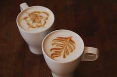 Två koppar av latte på den bruna trätabellen Arkivfoton
