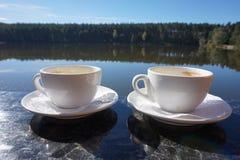 Två koppar av morgonkaffe som står på sidan av balkongen, med en magisk sikt av sjön arkivfoto