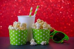 Två koppar av popcorn, drink och exponeringsglas för film på röd bokehbakgrund, selektiv fokus royaltyfri bild