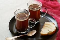 Två koppar av svart kaffe med en smörgås Royaltyfri Foto