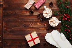 Två koppar av varm kakao eller choklad med marshmallowen, gåvor, tumvanten, juldekoren och granträdet på träbakgrund över Arkivbild
