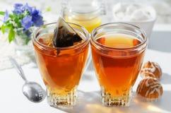 Två koppar av varm tepåsar, kakor och honung Processen av att brygga te Selektivt fokusera royaltyfria bilder