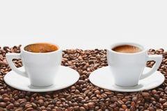 Två koppar av varmt kaffe med kaffebönor på vit bakgrund Royaltyfri Foto
