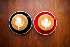 Två koppar av varmt kaffe med lattekonst på trätabellen Favorit- dryck av caffeindrinken fotografering för bildbyråer