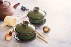Två koppar för grönt te för porslin för traditionell kines står på en grå tabell arkivfoto