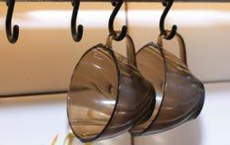 Två koppar för svart kaffe som hänger på krokar royaltyfri bild