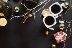 Två koppar kaffe, filialer, stearinljus och julleksaker på en mörk bakgrund Lekmanna- lägenhet arkivbilder