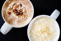 Två koppar kaffe i svartvitt på den svarta tabellen Royaltyfri Foto