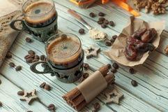Två koppar kaffe i tappningmetallkoppar, en ask av halwa, data, kaffebönor, muttrar och kanel Arkivbild