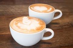 Två koppar kaffe lattekonst royaltyfri bild