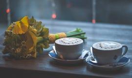Två koppar kaffe med en bröllopbukett Arkivbild