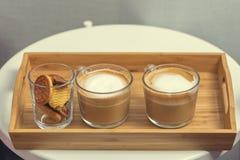 Två koppar kaffe med mjölkar på ett magasin Arkivfoto