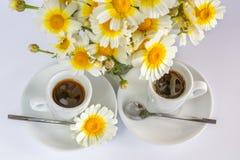 Två koppar kaffe och en bukett av kamomillar Royaltyfri Foto