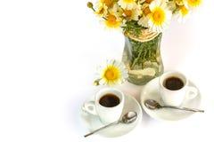 Två koppar kaffe och en bukett av kamomillar Arkivbilder