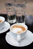 Två koppar kaffe och vatten Fotografering för Bildbyråer