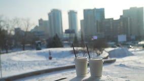Två koppar kaffe på en snö och en vinterstad arkivfilmer