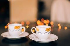 Två koppar kaffe på tabellen på bakgrundsbokeh arkivfoto