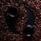 Två koppar kaffe, stjärnaanis och kaffebönor på en mörk kökcountertop i form av Feng Shui Doftande kryddor för drink, arkivfoto