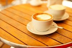 Två koppar med cappuccino (varmt kaffe med mjölkar), Fotografering för Bildbyråer