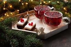Två koppar med den kryddiga drinken för varm jul med tranbäret och kakor royaltyfri bild