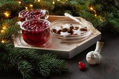 Två koppar med den kryddiga drinken för varm jul med tranbäret och kakor fotografering för bildbyråer