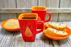 Två koppar med espressokaffe, rå farin och amandelcantu Arkivbild
