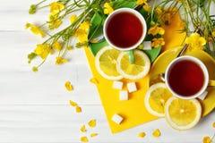 Två koppar med te och citronen är på trätabellen Arkivbilder