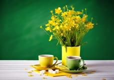 Två koppar med te och citronen är på trätabellen Vas med gula smörblommor på en grön bakgrund Arkivfoto