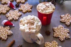 Två koppar och marshmallower för varm choklad, mot grå bakgrund & julsammansättning med snöflingapepparkakakakor royaltyfria foton