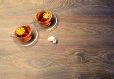 Två koppar på rätt nära spisen på tappningträtabellen Co royaltyfria bilder