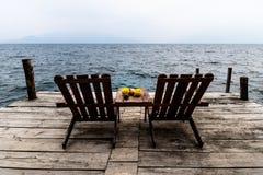 Två koppla av stolar på pir med frukter på Santa Cruz de Laguna, sjö Atitlan, Guatemala Royaltyfri Fotografi