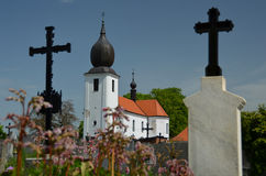 Två kors och en kyrka i en kyrkogård Arkivfoto
