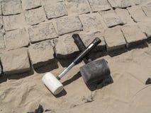 Två korsade rubber hammare ligger på oavslutat lägga av förberedande stenar för granit royaltyfria bilder