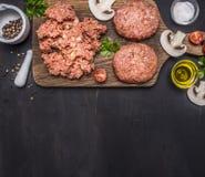 Två kotletter för hamburgare med köttfärs på en skärbräda med örter, salt gräns för smör, ställetext på trälantliga lodisar Royaltyfria Bilder