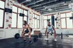 Två kraftiga grabbar i idrottshall lyfter skivstånger royaltyfri foto