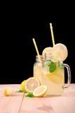 Två krus för en murare av ett vatten och mogna och saftiga citroner, en grön ny mintkaramell och med gult rakt sugrör på en svart Royaltyfri Foto