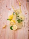 Två krus för en murare av ett vatten och saftiga citroner, ny minut Ny lemonad med limefrukter och citroner i krus på en ljus trä Arkivfoton