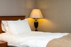 Två kuddar på säng och lampa på trätabellen Royaltyfria Foton