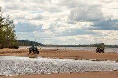 Två kvadratcyklar med ryttare rider längs kusten med en härlig sikt arkivbilder