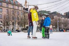 Två kvinna och barn som utomhus åker skridskor på en offentlig skridskoåkningisbana i staden Arkivbilder